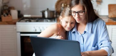 A woman wearing glasses sitting at a kitchen table wit her daughter looking at a laptop, representing how one can benefit from calling a Chicago child time-sharing attorney.