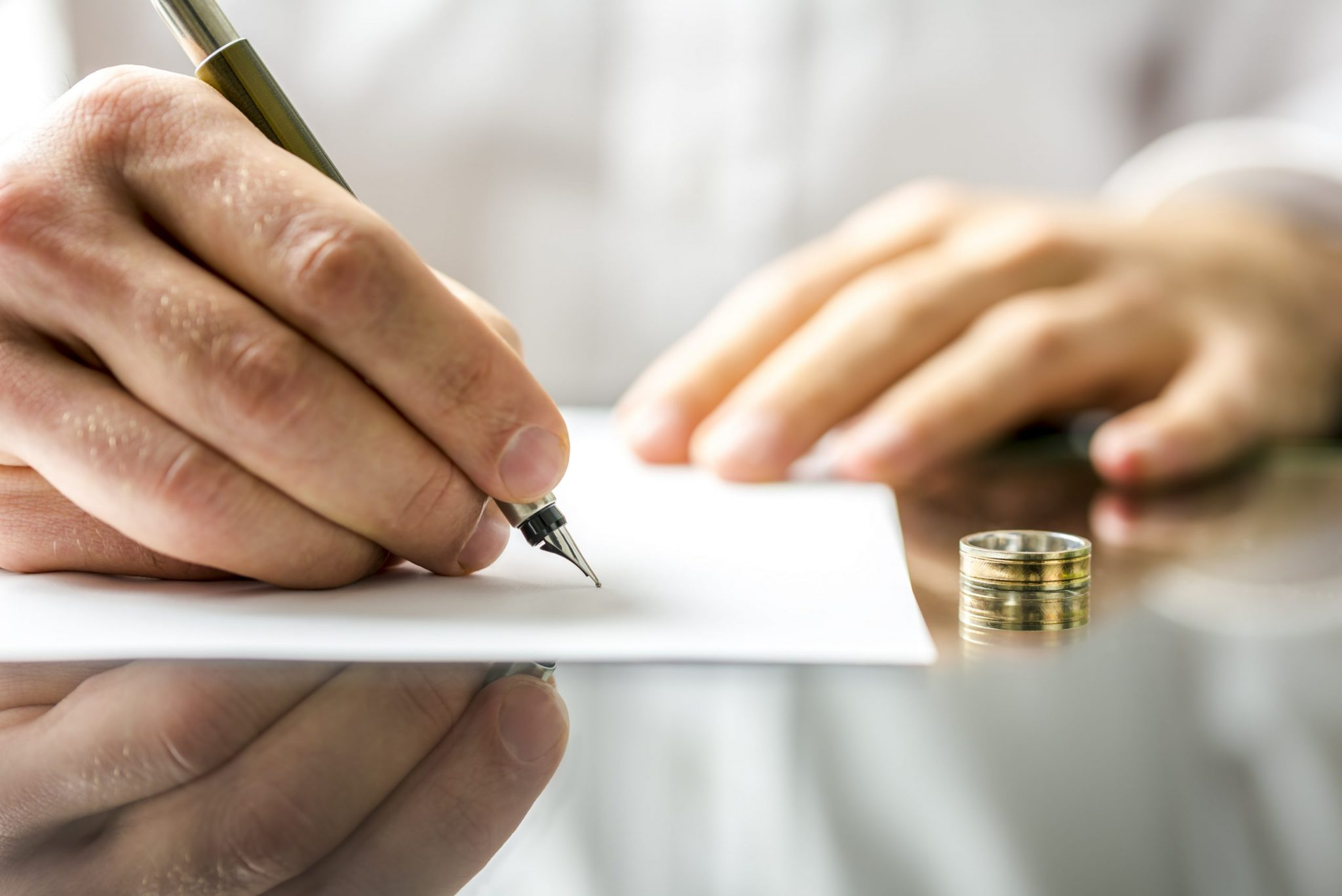 An upset woman taking off her wedding band in the foreground with an sad man in the background, representing how our Lincoln Park divorce attorneys can represent you in your divorce case.