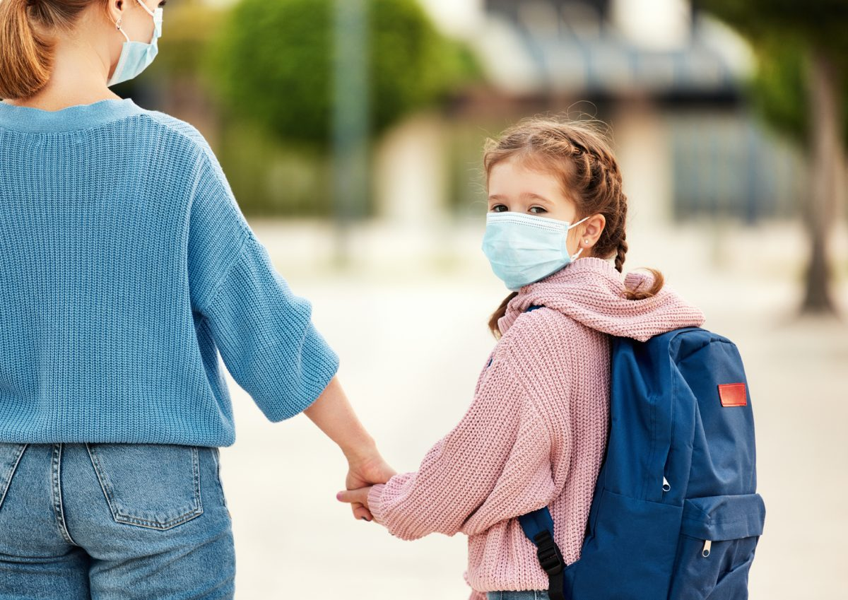 A girl that is wearing a mask and holding her mother's hand, speak to Cook County Child Custody Lawyer to change your parenting plan during the pandemic.