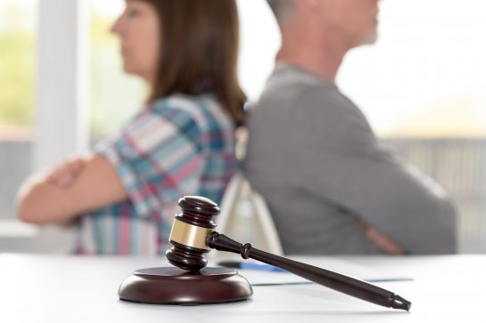 Woman and man sitting back to back with judge's gavel, turn to the Divorce Lawyers Oak Brook when needing to develop a parenting plan.