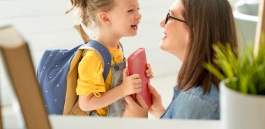 Small girl with backpack greeting her mom, to arrange a fair custody agreement work with a Chicago Parenting Time Lawyer.
