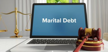 Marital debt on a laptop with gavel, contact Chicago Property Division Attorney when needing guidance on marital assets.