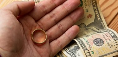 Wedding band in hand with money on table, needing good Divorce attorneys Chicago to look over alimony case.