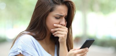 Woman checking her phone texts, if feeling like you are being harassed by ex via texting meet with your Chicago family law attorney.
