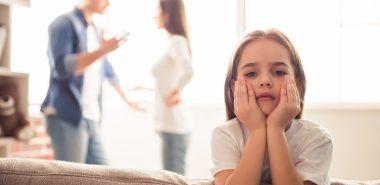A sad girl and her parents arguing in the background, meet with a Chicago Divorce Attorney to discuss your situation.