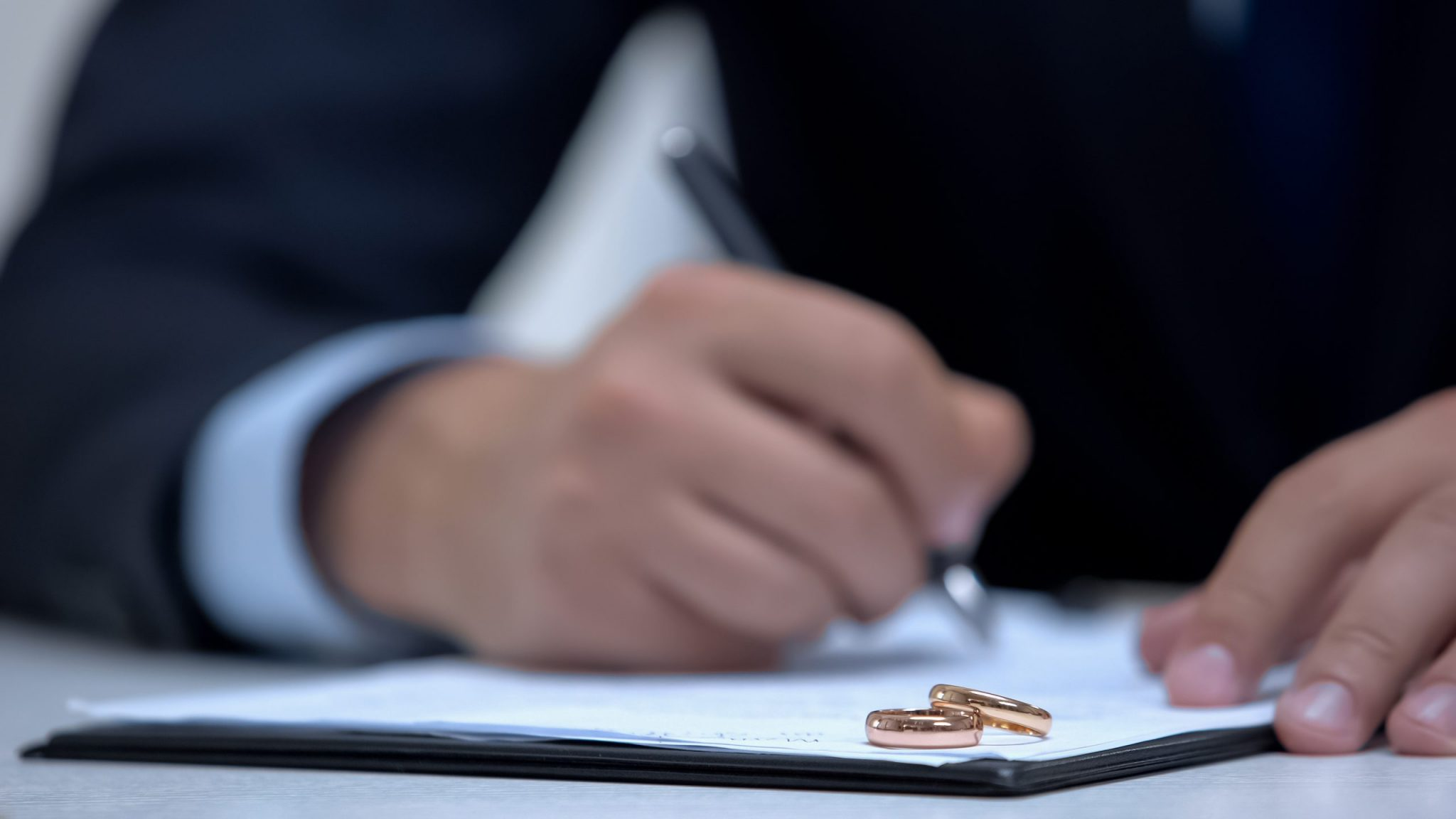 An image of two wedding rings lying on a divorce document, discuss your case with a Highland Park family law attorney